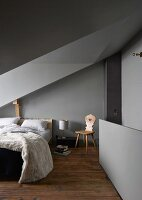 Grey walls and ceiling in attic bedroom with sloping ceiling and dormer window