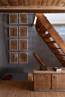 Old wooden stairs, wooden trunk and floral pictures in rustic hallway
