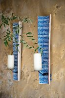 Two candle sconces made from painted roof tiles mounted on wall