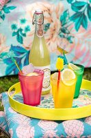 Summer drinks in colourful glasses and bottle on tray