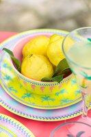 Lemons in bowl on colourful plate