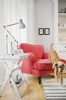 A dog jumping off a red armchair with a reading lamp and a tray table
