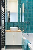 Bathtub and turquoise tiles in narrow bathroom