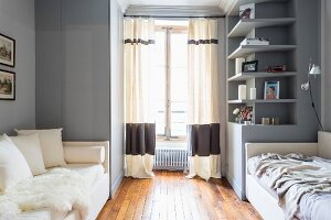 Two couches and grey walls in spare bedroom
