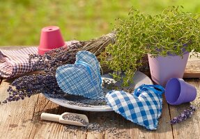 Hand-made, heart-shaped lavender sachets on table outdoors