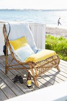 Yellow and white cushions on rattan easy chair on deck next to beach
