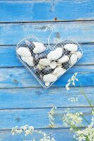 Love-heart made from wire mesh and coathanger filled with shells hung on board wall