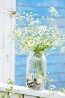 Flowers in preserving-jar vase with pebbles in bottom