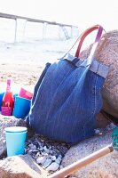 Denim bag and colourful beakers on beach