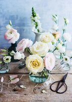 Glass vase of pale pastel roses and ranunculus