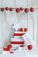 Christmas presents wrapped in red and white and red baubles against board wall