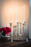 Lit candles in various silver candlesticks on tray and small vase of roses