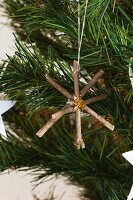 Star made from twigs hanging on Christmas tree