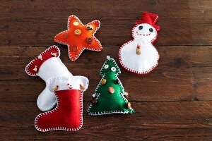 Hand-made felt Christmas decorations (stocking, snowman, Christmas tree and star) on wooden surface