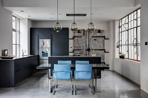 Dining table and blue chairs in open-plan kitchen of industrial loft apartment in shades of grey