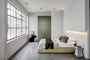 Bedroom in industrial loft apartment with concrete floor and factory windows