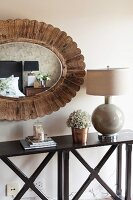 Oval mirror with wooden frame above console table with cross-braced frame