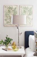 Bedside lamp with silver base and two bird ornaments below botanical illustrations on wall