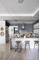 Breakfast bar and industrial-style bar stools in modern, open-plan kitchen