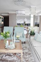 Two pale blue armchairs in elegant interior in pale shades of grey