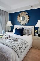 Mirror on rich blue wall above bed in elegant bedroom