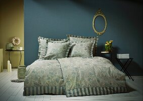 Scatter cushions with flanged edges on bed in blue and green bedroom
