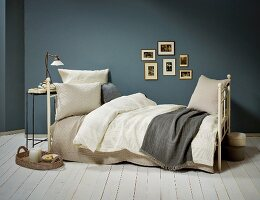 Vintage-style metal bed with pillows and blankets in natural shades against blue-grey wall
