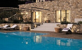 Modern stone house with terrace and pool; twilight atmosphere with candles and lights