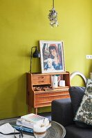 Picture on top of retro writing desk against mustard-yellow wall