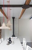 Various pendant lamps suspended from red cords above table