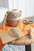 Parcel string, cardboard and scissors for making tassels