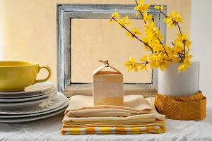 Stacked white plates, yellow cup, table linen and flowering forsythia branches