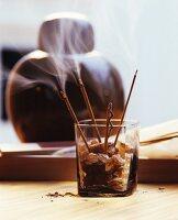 Glowing scented joss sticks in glass of rock sugar
