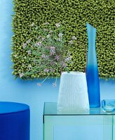 Allium flower and two vases in front of green wall-hanging