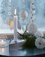 Lit white candle in festive, silver and white, glittering ambiance