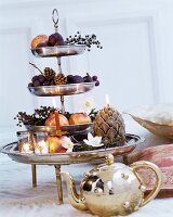 Fruit, artificial flowers and candles arranged on shiny silver cake stand behind shiny gold teapot