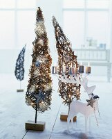 Lit pillar candles on white, stag-shaped candle holder in front of two small, wicker, Christmas tree ornaments