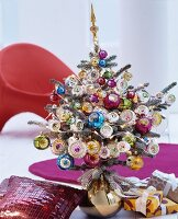 Small Christmas tree lavishly decorated with colourful baubles standing in gold vase