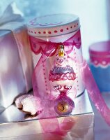 Tin decorated with pink ribbon and original Christmas tree bauble