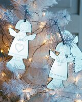 Angle decorations and fairy lights on white artificial Christmas tree