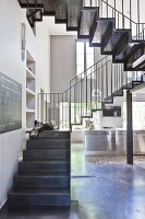 Delicate metal staircase in loft apartment in shades of grey