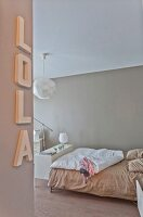 Bedroom in soft beige shades with decorative letters on wall