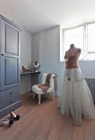 Tailors' dummy wearing underskirt in front of dressing table and easy chair