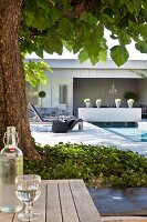Bottle and glass of water in front of tree, swimming pool and loungers