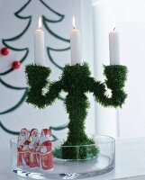 Candelabra covered in artificial pine needles and chocolate Father Christmases in glass dish