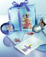 Arrangement of envelopes, baubles and wrapped gift decorated with cartoon motifs