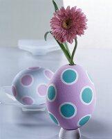 Pink gerbera daisies in egg-shaped vase painted in pastel shades