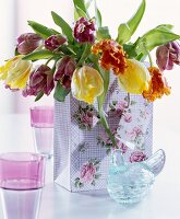 Bouquet of tulips in rose-patterned gift bag and vintage-style hen-shaped glass jar