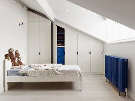 Child's attic bedroom with wardrobes fitted under sloping ceiling