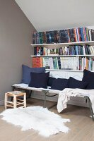 Scatter cushions on camp bed below bookcase under sloping ceiling